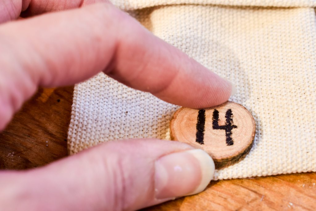 gluing a wood slice with the number 14 to drop cloth bag