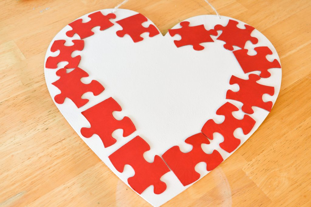 red puzzle pieces arranged around the perimeter of a wooden white painted heart