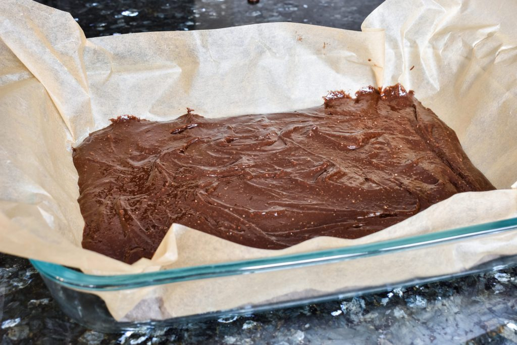 brownie batter in a 13 by 9 inch baking pan atop parchment paper