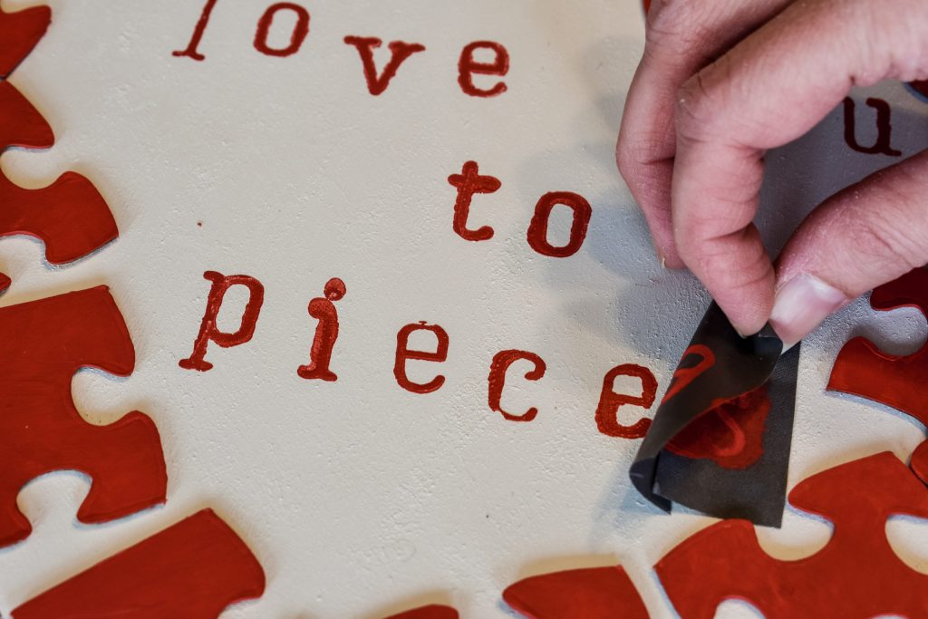 removing a letter stencil from a white painted wooden heart wall hanger