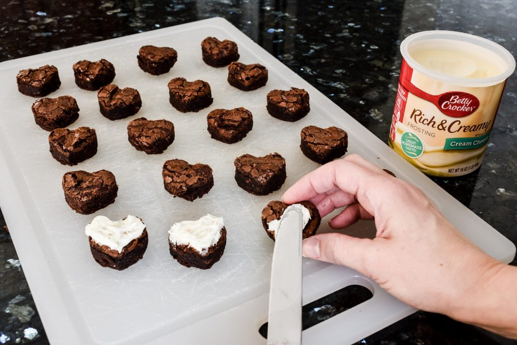 icing heart shaped brownies with white cream cheese frosting