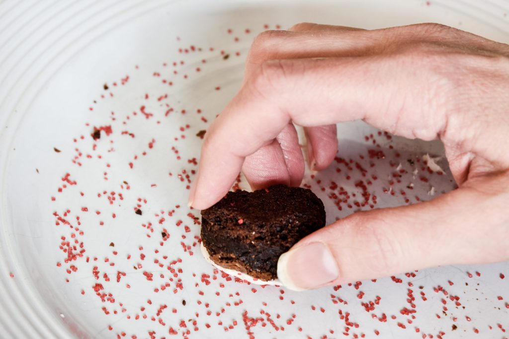 dipping a frosted brownie into a plate of red sprinkles