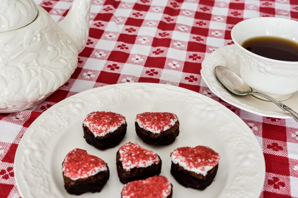 heart shaped brownie bites with red and white frosting and sprinkles