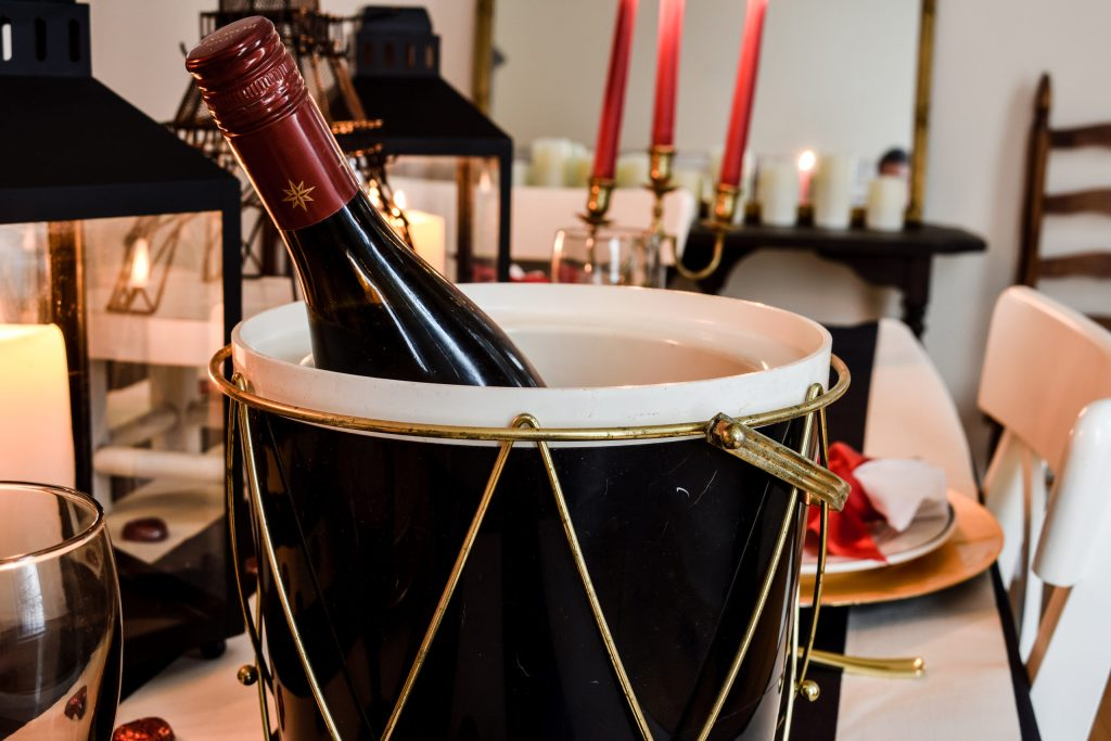 vintage black ice bucket with gold trim holding a bottle of red wine