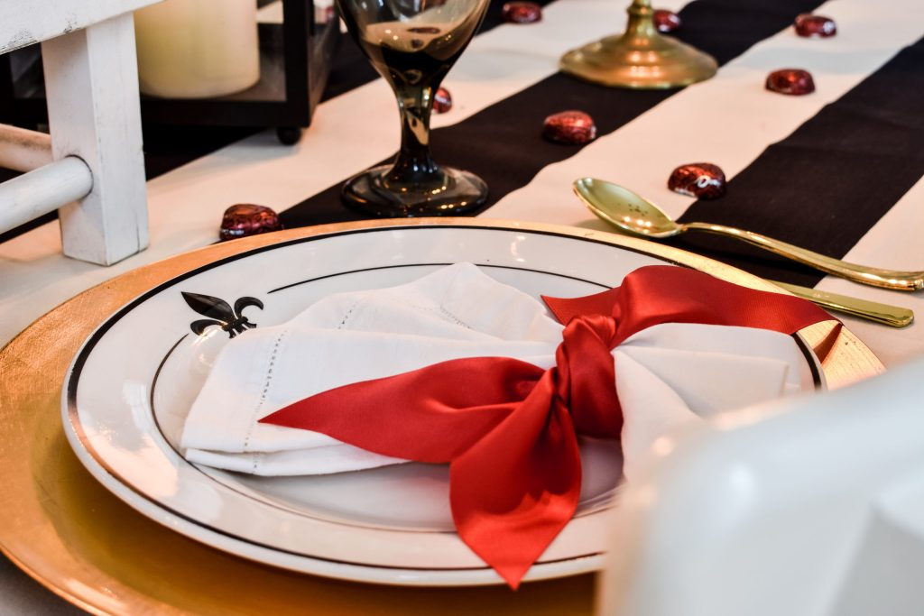 white plate with a fleur-de-lis motif on a gold charger topped with a white linen napkin tied with red ribbon
