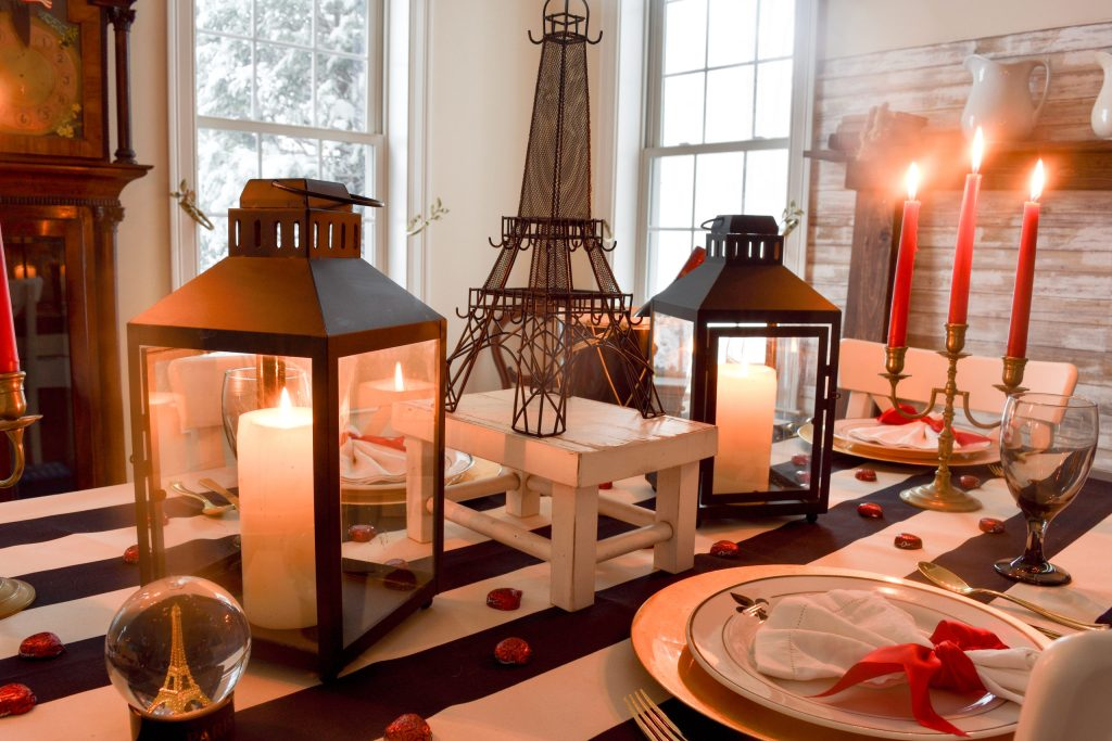 Eiffel Tower centerpiece, a pair of black lanterns and fleur-de-lis plates on a Valentine's Day in Paris themed tablescape