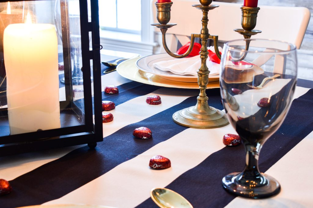 black and white striped tablecloth with a lantern, black drinking glass, red chocolates and a candelabra