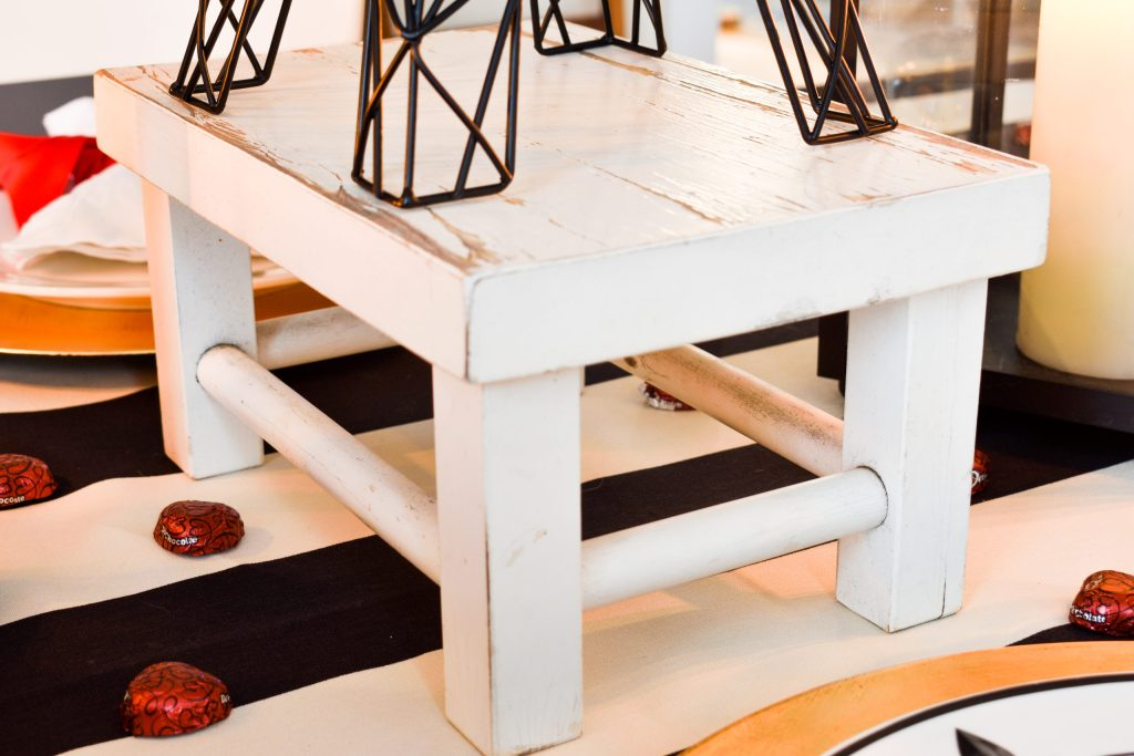 small white stool used as a riser for the Eiffel Tower  in a Paris themed Valentine's tablescape