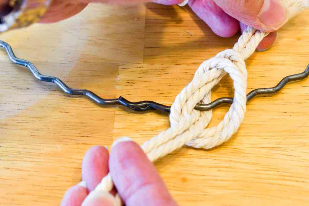 tying a knot of two strands of cord on a metal hoop
