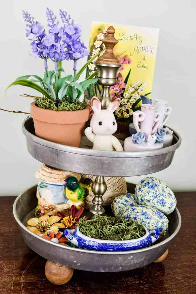 Easter tiered tray styled with faux potted lavender, a vintage greeting card, mini bud vases, fabric covered Easter eggs, vintage floral brooches, a moss filled trinket dish, and a mini bunny