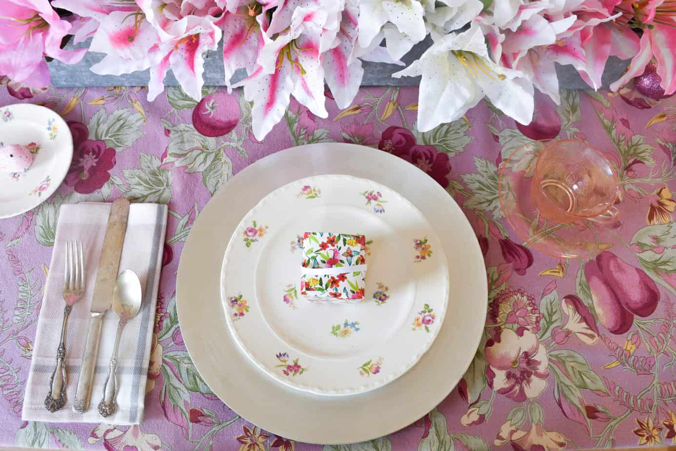 vintage floral plate atop a silver charger with a treat box on a pink Easter tablescape