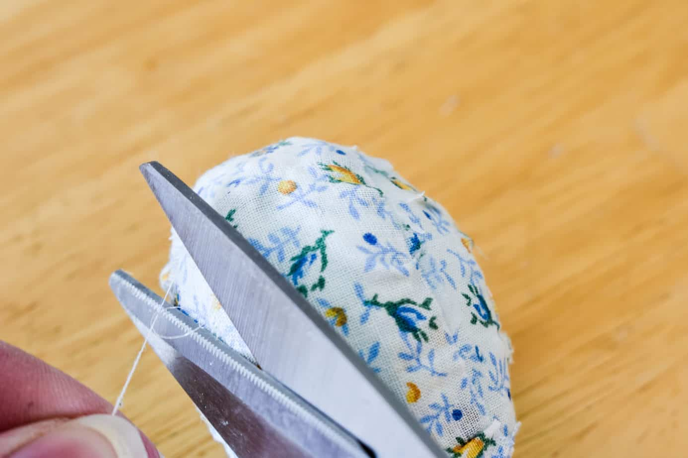 trimming loose string from a fabric covered Easter egg