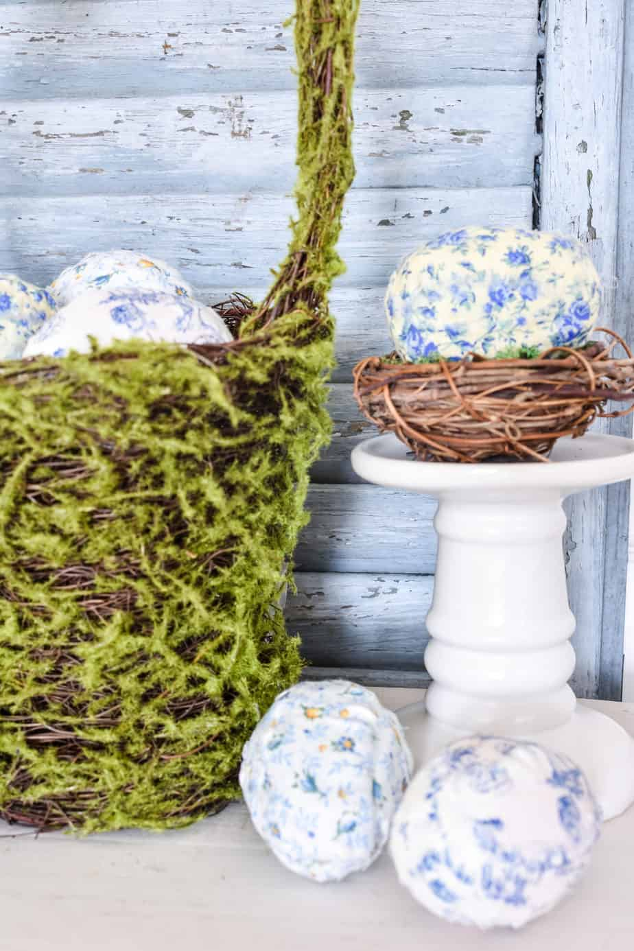 Fabric covered Easter eggs in a moss covered basket and in a grapevine nest