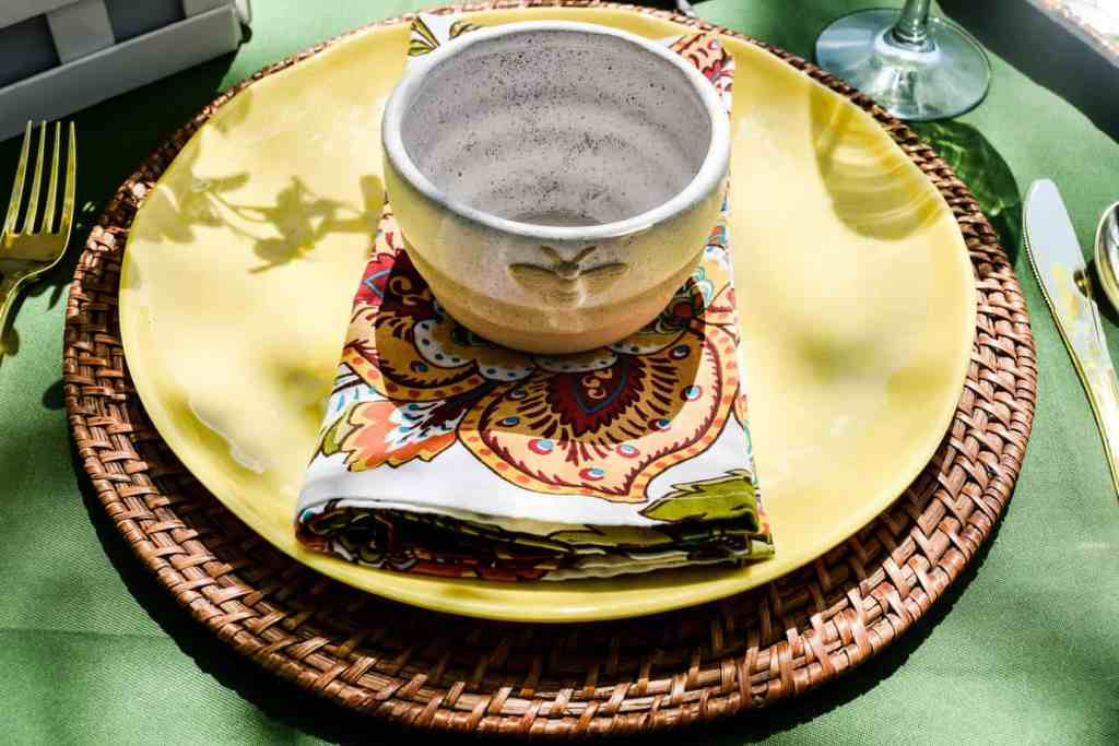 place setting with a rattan charger, yellow plate, floral napkin and a stoneware bowl with a bee motif on a bee themed tablescape