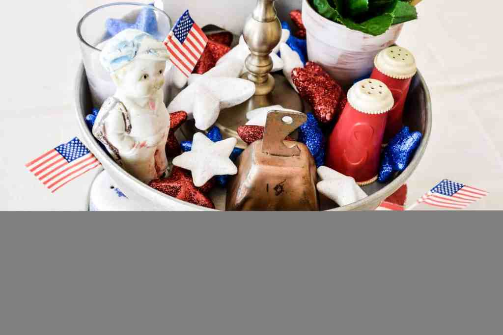 Patriotic home decor in a two tiered aluminum tray including red white and blue vintage finds and Dollar Tree items