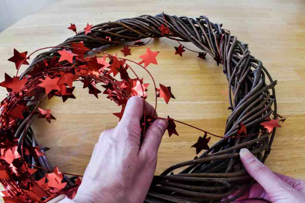 wrapping a red star garland around a grapevine wreath form to create a patriotic door wreath