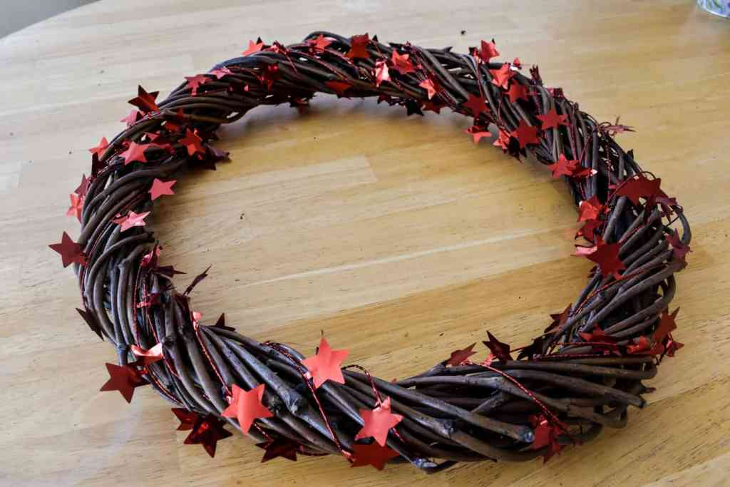 grapevine wreath form wrapped with several yards of red star garland to create a patriotic door wreath