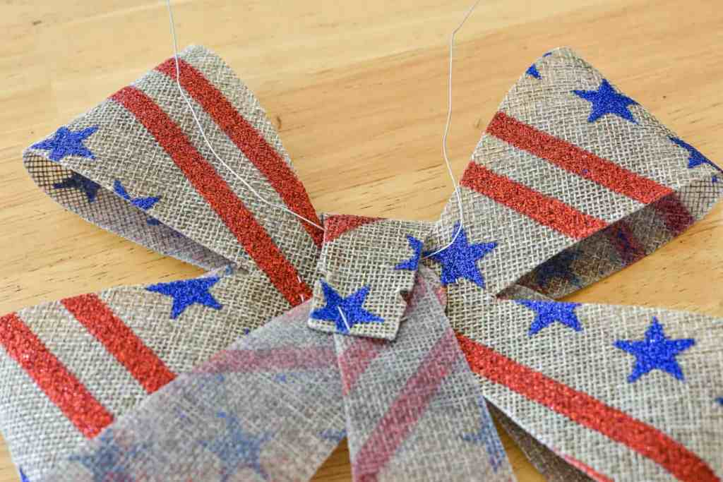 back of a burlap patriotic bow with a 12 inch length of floral wire threaded through the loop