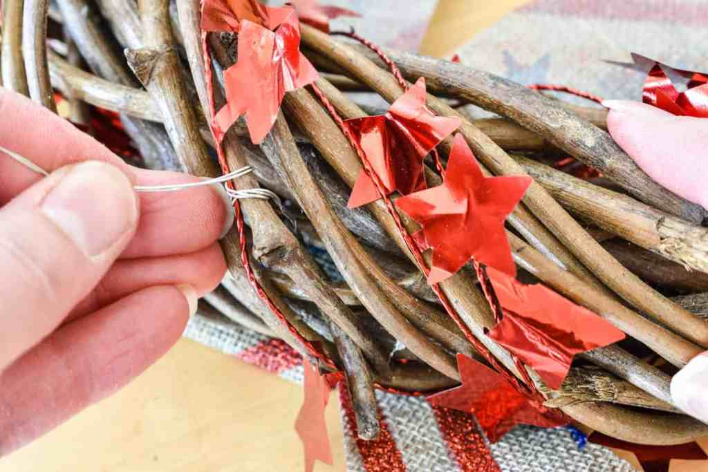 attaching a bow to a patriotic door wreath with floral wire