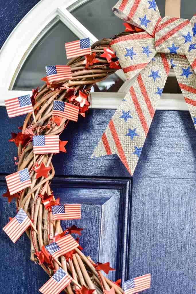 how to make a patriotic door wreath decorated with a red star garland, burlap bow and mini American flags