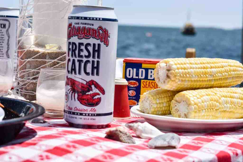 can of Fresh Catch beer with a lobster motif and a platter of corn on the cob