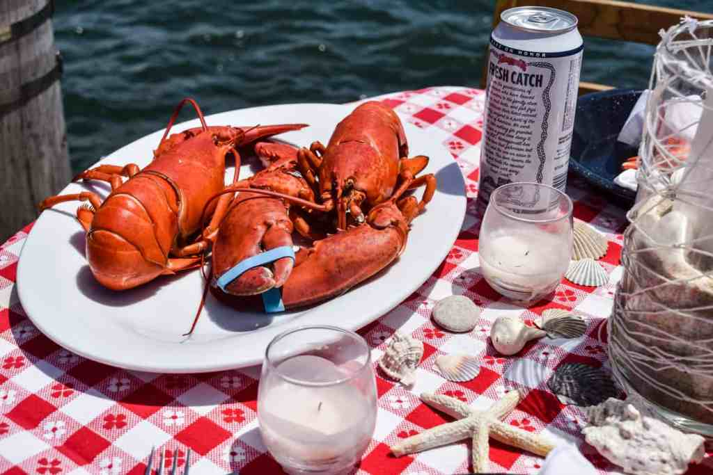 two steamed lobsters on a white platter, shells and candles on a seafood theme table setting