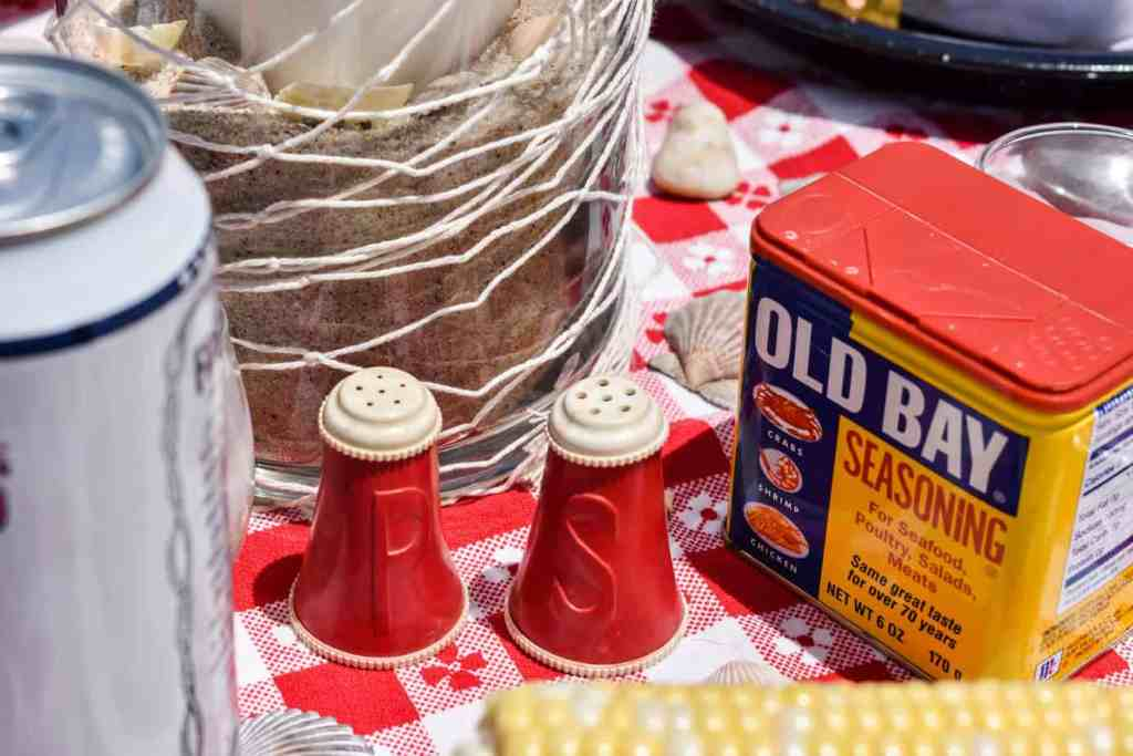 vintage red plastic salt and pepper shakers and a tin of old bay seasoning
