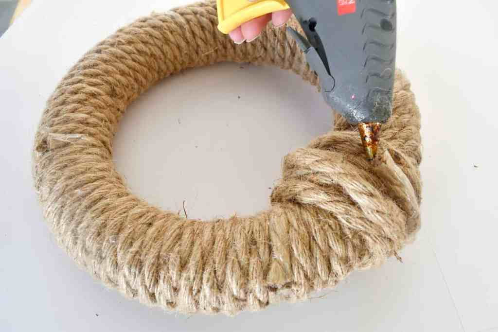 securing the last piece of rope with hot glue to a wreath