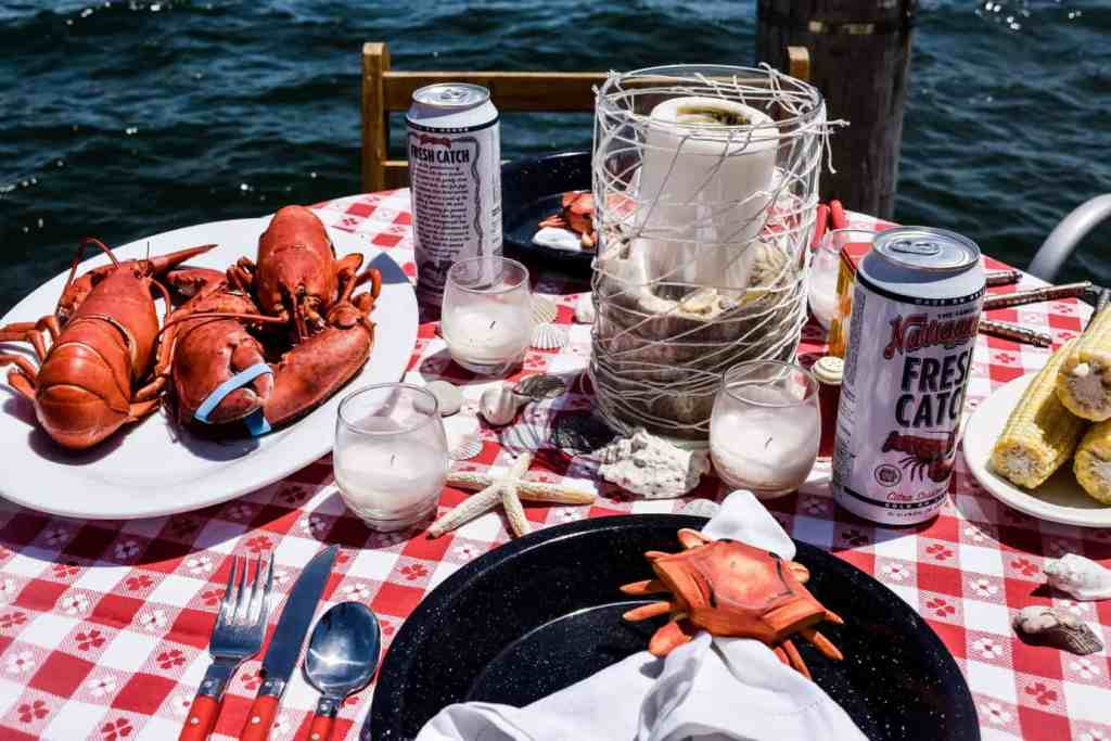 lobster table setting with a red and white check tablecloth, shells, steamed lobsters, beer, corn on the cob, candles and enamelware plates.