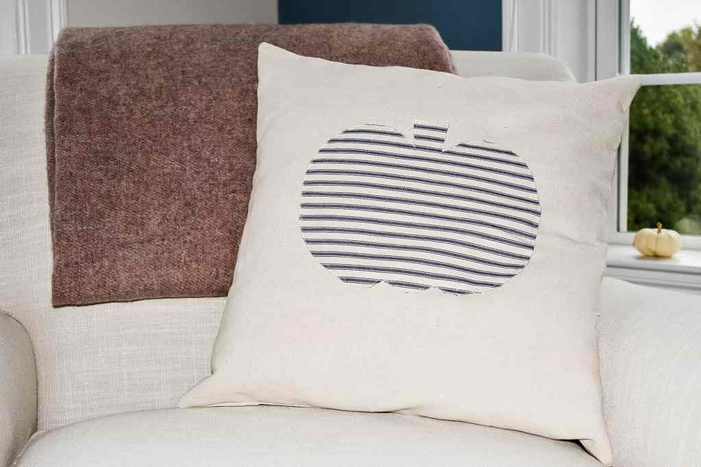 pillow made from drop cloth with a pumpkin appliqué made from blue and white ticking strip fabric