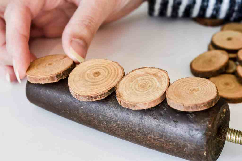 placing small wood slices onto a wooden furniture leg