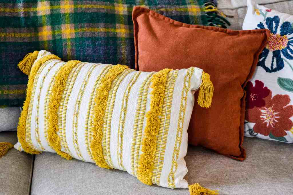 yellow striped tassel pillow, solid rust colored throw pillow and a multicolored embroidered floral pillow provide fall decor on a couch