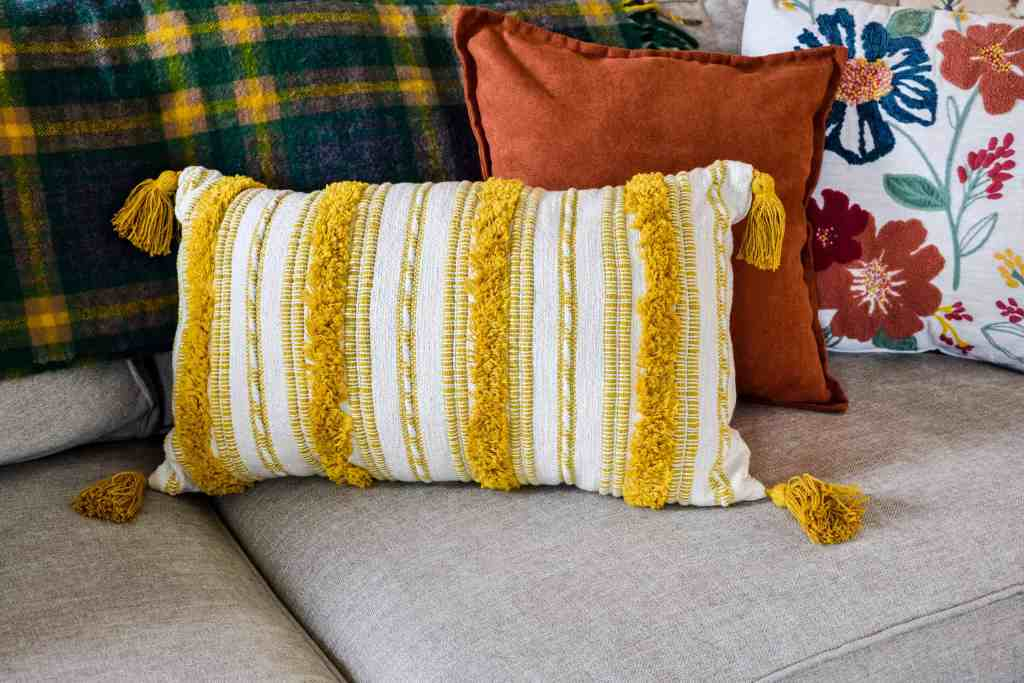oblong yellow striped pillow with tassels, a solid orange pillow and a floral multicolored embroidered pillow on a couch.