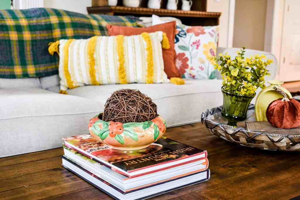 wood coffee table with books and a tray with fall decor in front of a couch filled with colorful fall throw pillows