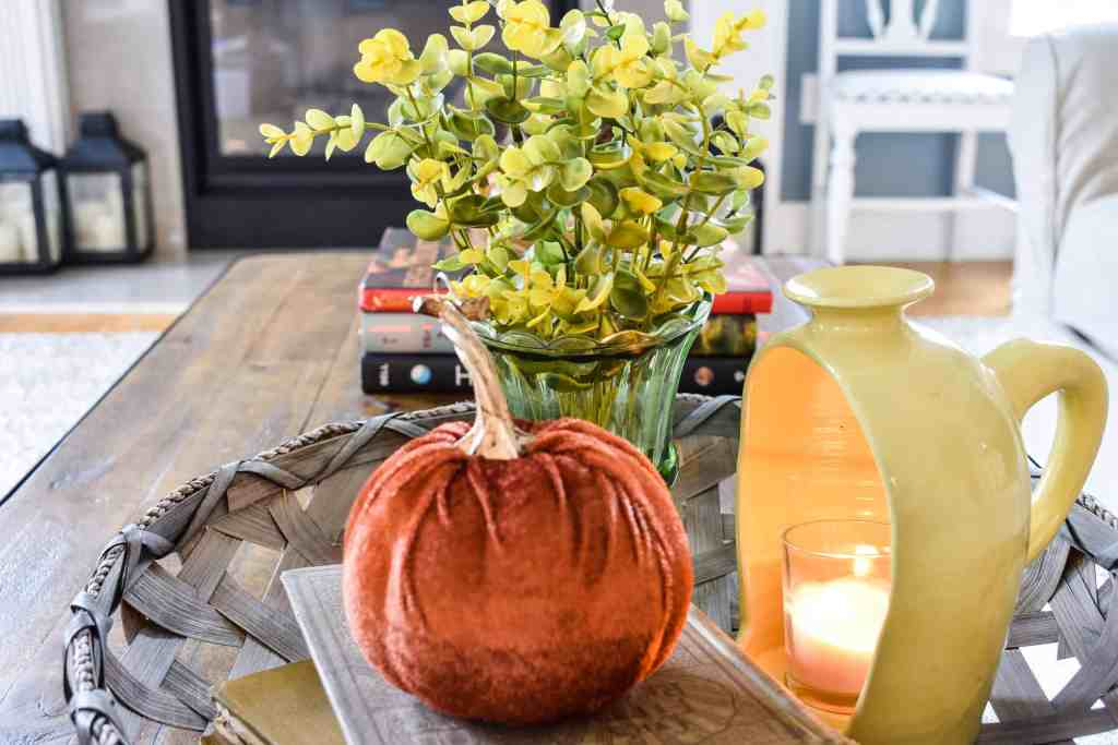 round basket tray on a coffee table filled with fall decor including old books, a yellow half jug ceramic lantern, an orange velvet pumpkin and a green glass urn filled with faux green and yellow florals