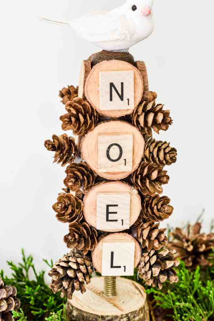 wooden Christmas tree made from an old wooden furniture leg decorated with wood slices, pinecones, Scrabble tiles that spell NOEL and a faux white bird