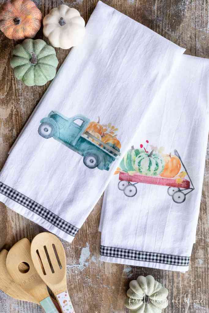 two white tea towels stamped with a truck filled with pumpkins and a red wagon filled with pumpkins