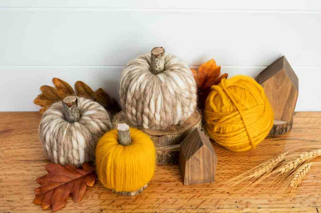 yellow and brown yarn wrapped pumpkins with sticks for stems