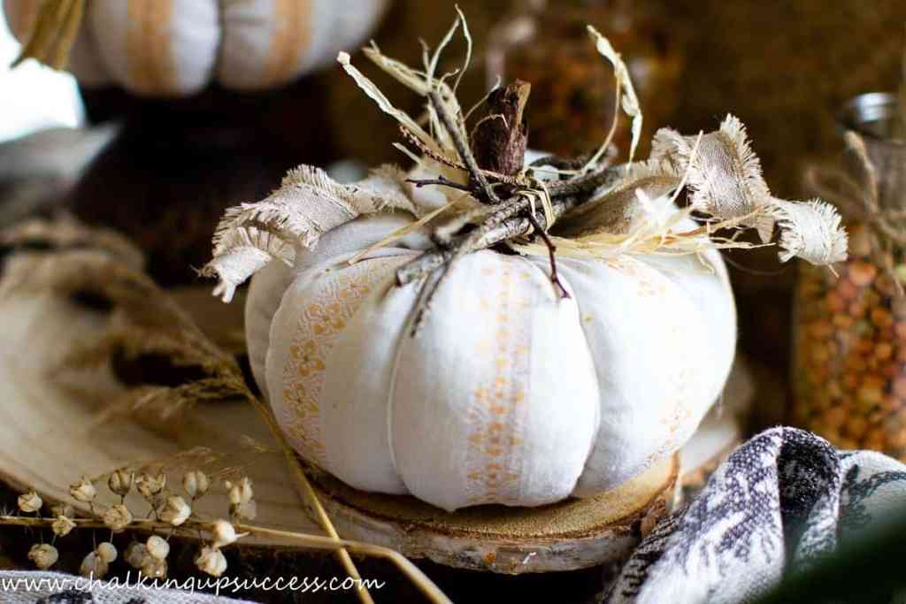 rustic white fabric pumpkin decorated with twigs, raffia and tattered ribbon