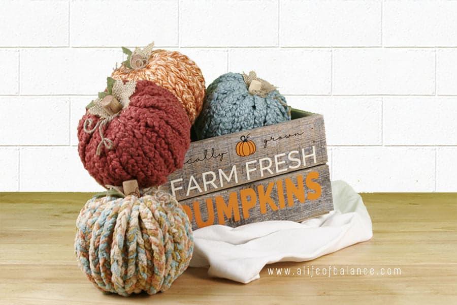 chunky yarn pumpkins in fall colors displayed in a farm fresh pumpkins box