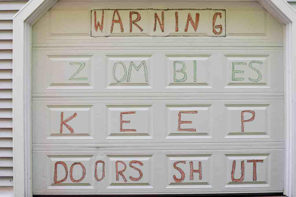 garage door with a zombie warning written in chalk