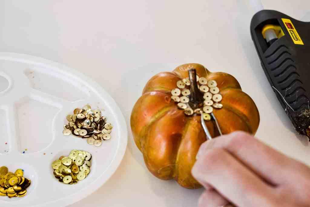 hot gluing gold sequins to a sequin craft pumpkin with tweezers