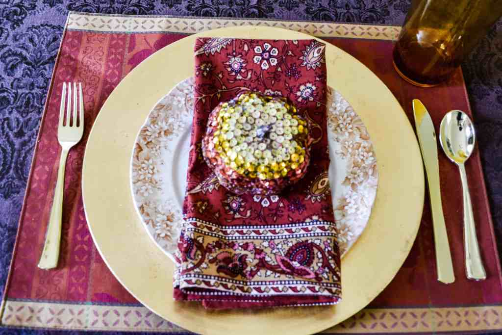fall Tablescape place setting overhead shot with a rust placemat, gold charger, vintage brown floral plate, and rust napkin with a sequin pumpkin on top.