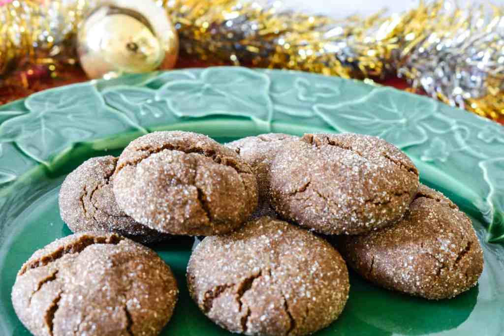 green plate filled with old fashioned ginger snap cookies styled with tinsel and a gold Christmas bulb ornament
