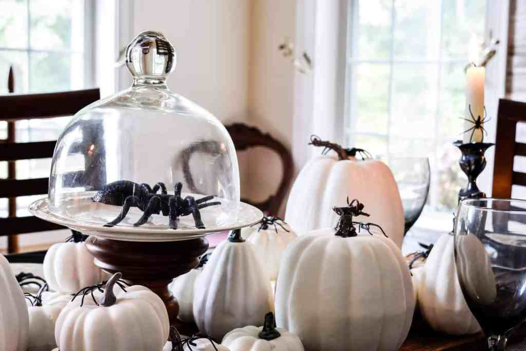 black spider under a glass cloche amid white pumpkins on a spider themed Halloween tablescape