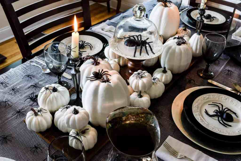 centerpiece of white pumpkins with spiders and a glass cloche overtop a black plastic spider on a Halloween tablescape