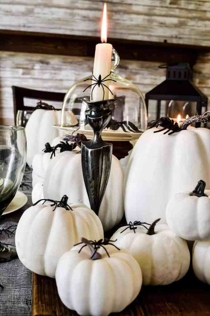 centerpiece of white pumpkins, black plastic spiders and a lit taper candle on a Halloween tablescape