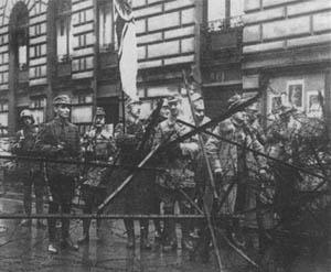 9. November 1923: Barrikade bewaffneter SA-Männer. Deutlich erkennbar Heinrich Himmler mit der alten Reichsflagge.