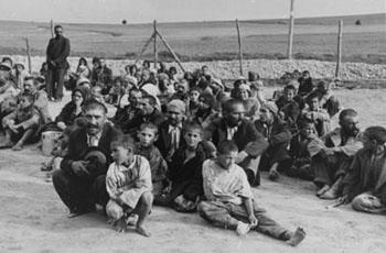 Eine Gruppe von Sinti und Roma nahe dem Zaun des KZ Belzec warten auf Anweisungen ihrer deutschen Bewacher. Belzec, 1940. Quelle: USHMM, courtesy of Archiwum Dokumentacji Mechanicznej.