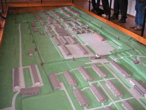 """Ein Modell zeigt die frühere Gestalt des Lagers. Außerhalb des Lagertores (Vordergrund) waren die Wachmannschaft und die Kommandantur untergebracht. In der Mitte befindet sich das Stammlager, dahinter das 1944 entstandene sogenannte """"Ausschwitz-Lager""""."""